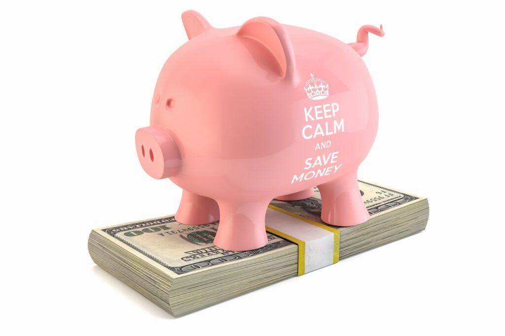"piggy bank saying ""keep calm and save money"" while sitting on top of a stack of one hundred dollar bills."